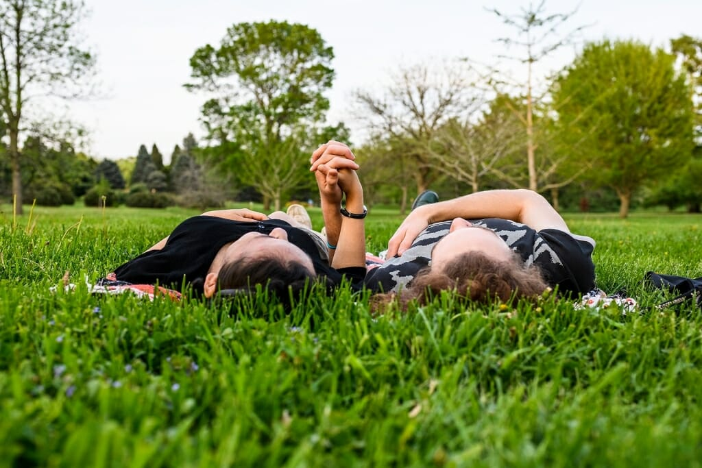 Photo: Two people lying on their backs in the grass, holding hands