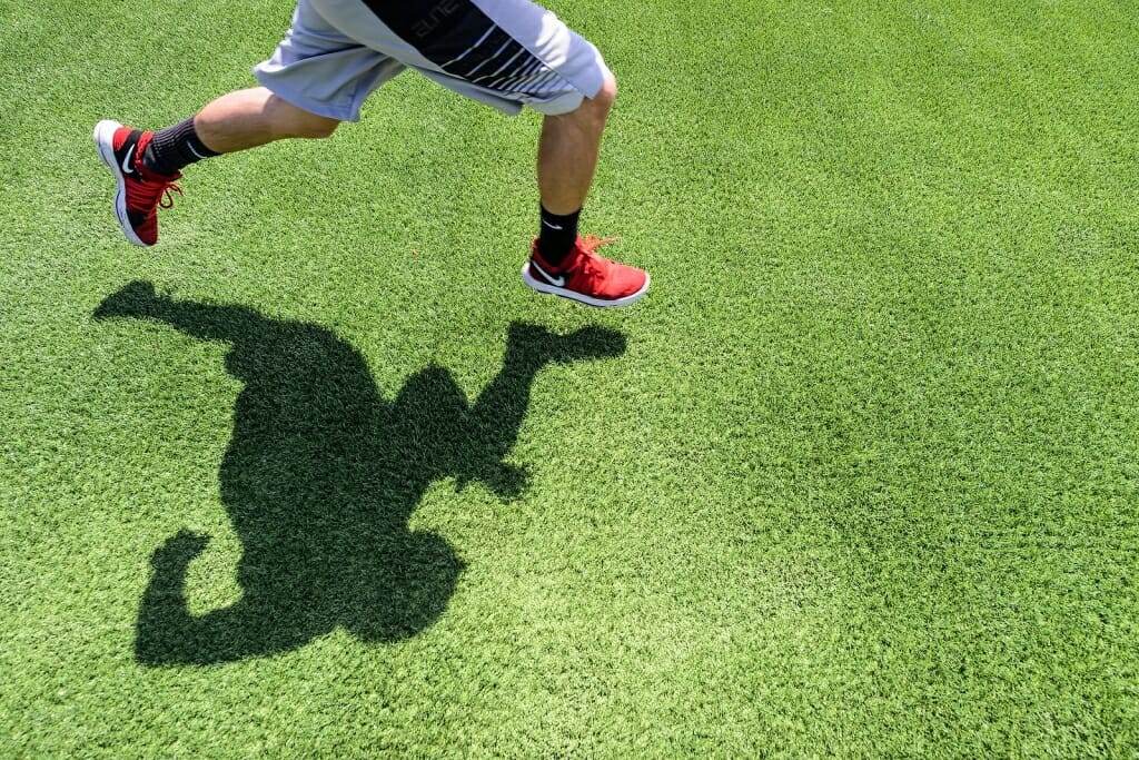 Photo: Closeup of legs of a runner casting shadow on the grass