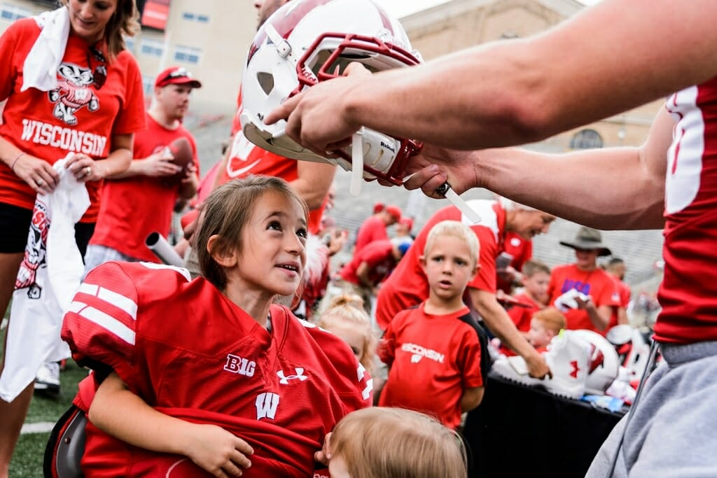 Photo: Football player placing helmet on girl's head
