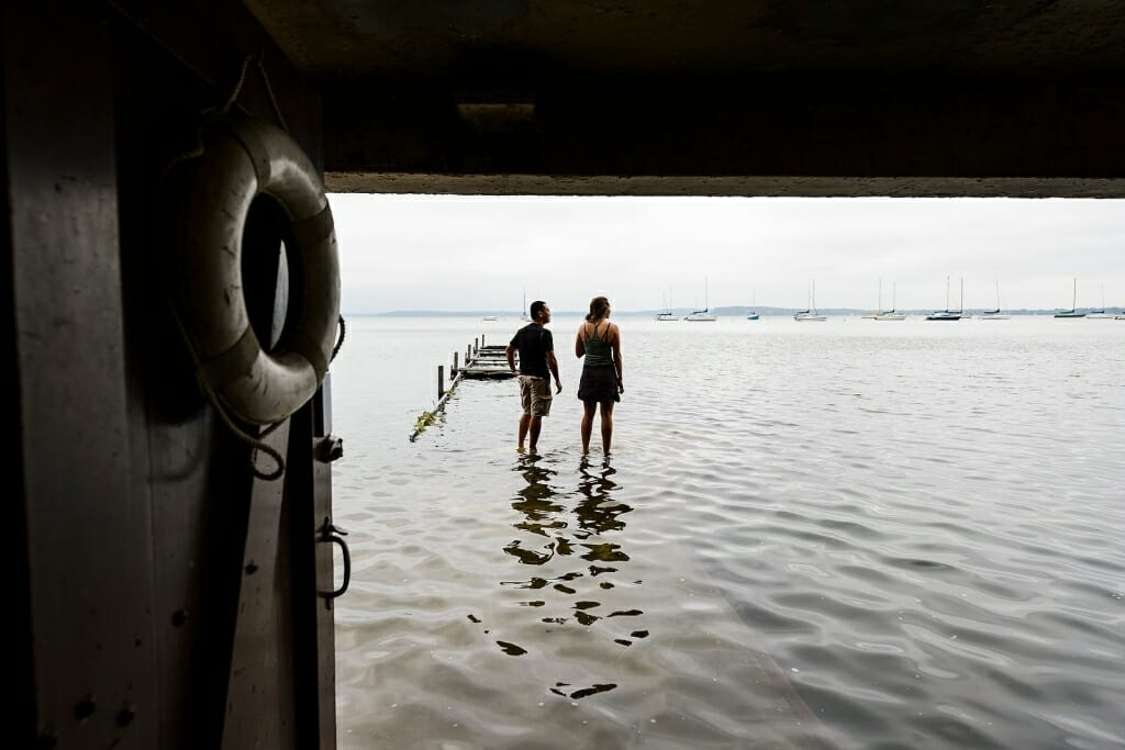 Photo: Two people standing on a partially submerged pier