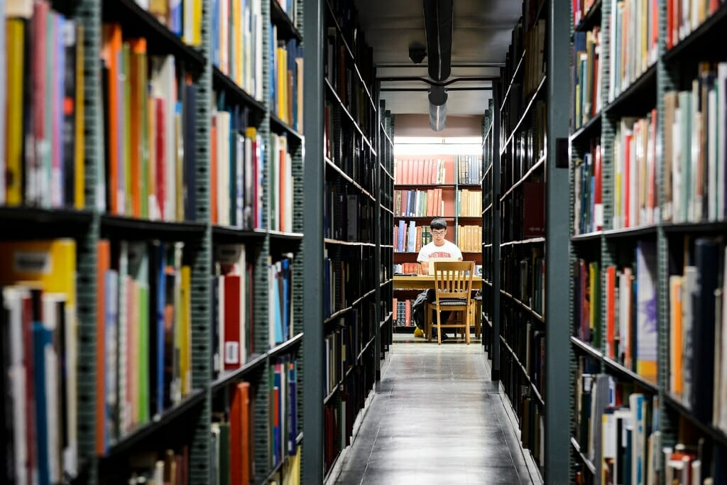 Photo: Person working on laptop as seen through two bookshelves