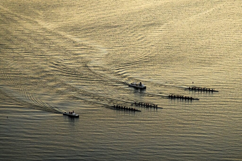 Photo: Aerial view of boats in water making ripples