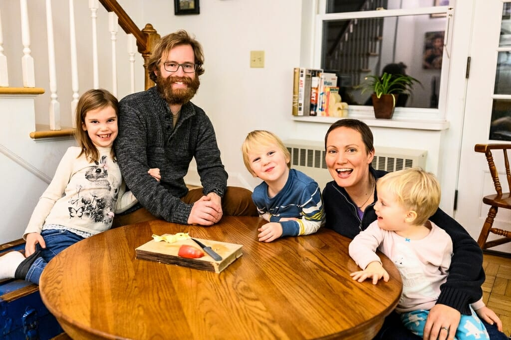 Photo of Noah and Noel Ash and their three children gathered around a table.
