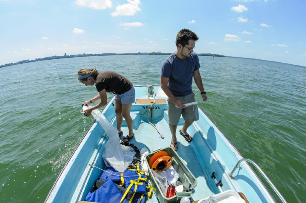 Photo: Walsh and Brosat on a boat, dipping nets into water