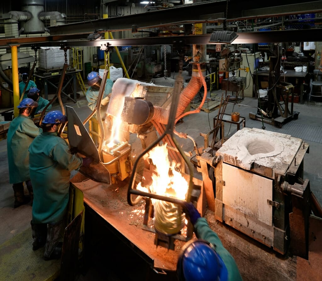 Photo: Workers pouring molten metal in foundry