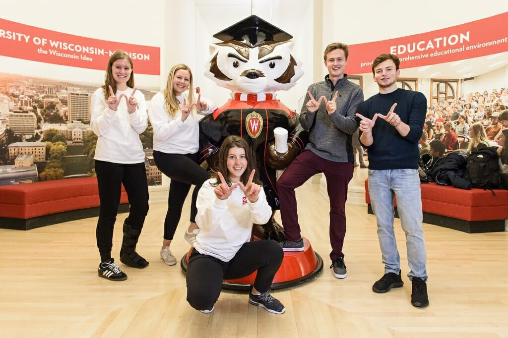Five people in front of a Bucky Badger statue.