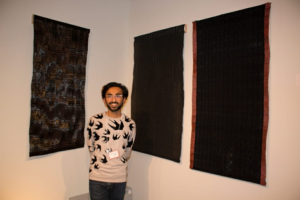 Photo: A man with some wall hangings he designed.