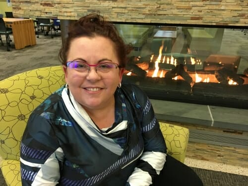 A photo of a woman in front of a fireplace. She's smiling.