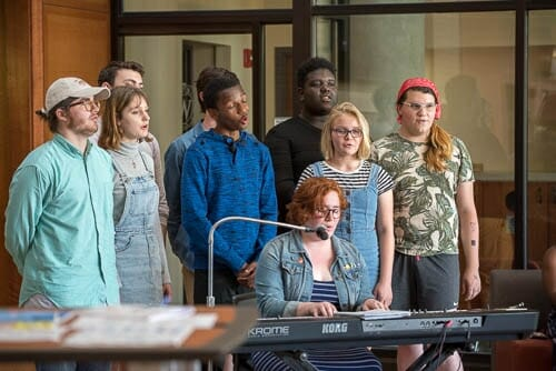 Photo: Students gather around a keyboard while a woman sings.