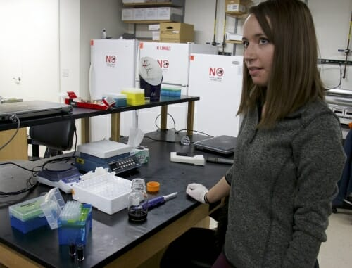 Photo: Student standing next to lab bench
