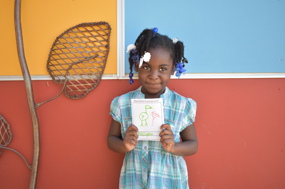 Photo: A girl holds a piece of paper and smiles.