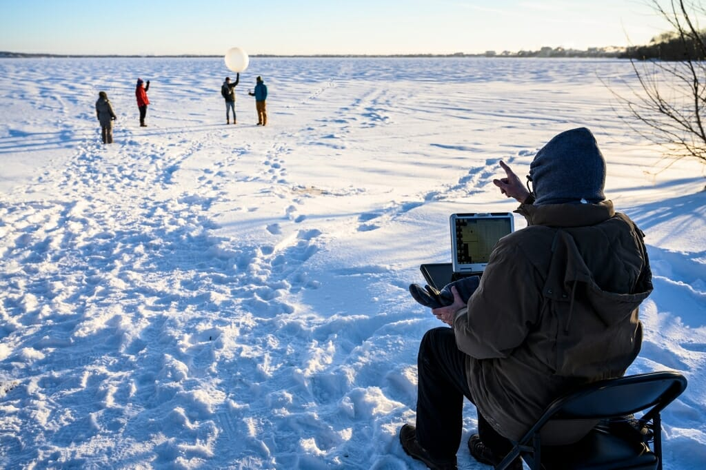 Students stand on frozen Lake Mendota poised to launch the weather balloon, now equipped with the radiosonde. Petty checked that the instrument was transmitting data to his computer and gave the students instructions prior to launch.