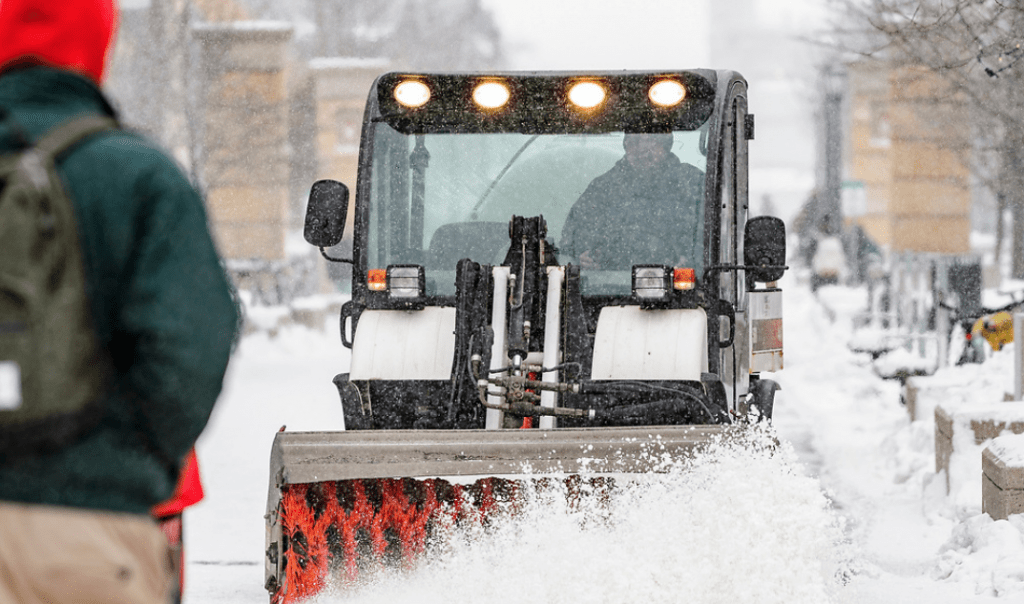 UW grounds crew members work to clear snow from the sidewalks on East Campus Mall at the University of Wisconsin–Madison