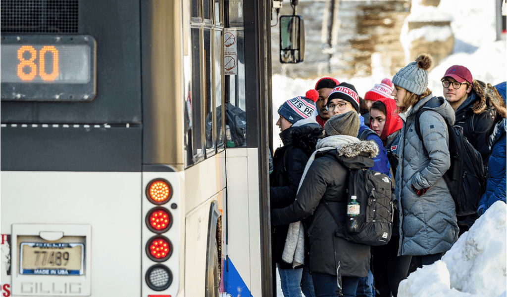UW students bundle up to stay warm as they wait to board the #80 bus as temperatures hover around zero degrees Fahrenheit.