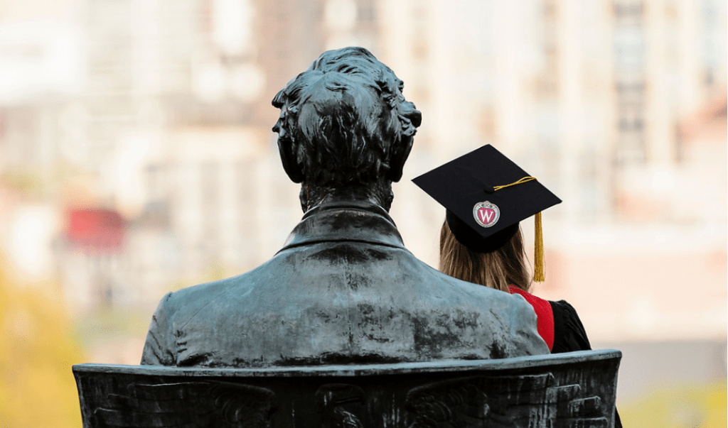 A soon-to-be graduate sits in the lap of the Abraham Lincoln statue on Bascom Hill.