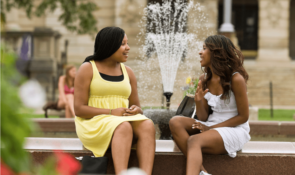 Students Bettina Billings (left) and Tessia Brown (right) spend a moment talking at the fountain on Library Mall.