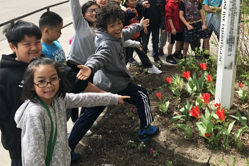 Photo: Children gesturing toward tulips