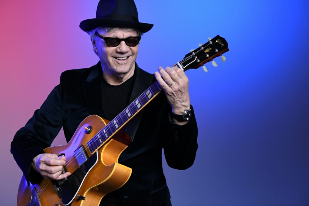 Photo: Steve Miller in dark glasses playing a guitar