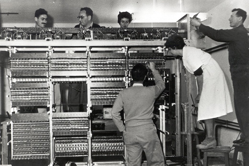 Photo: Several people standing by a large computer