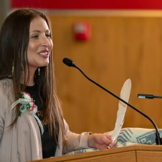 Melissa Metoxen is academic support coordinator for the Native American Center for Health Professions, at UW-Madison's School of Medicine and Public Health. She is holding an eagle feather that was presented to her during the reception by her grandfather, Korean War veteran Russell Metoxen.