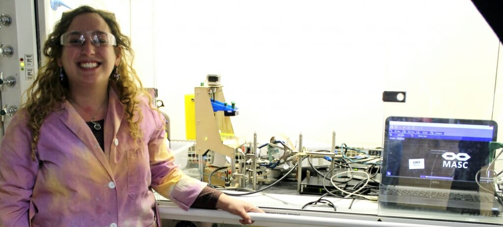 Photo: Woman with lab coat stands next to equipment.