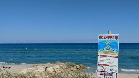 Photo of a sign posted near a beach warning of rip currents.