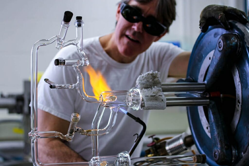 Photo: Drier in dark goggles working with flame on glass instrument