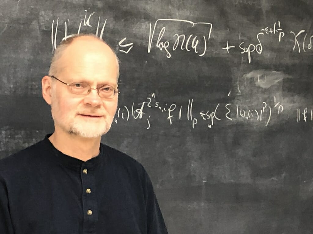 Photo: Andreas Seeger standing in front of a chalkboard with equation on it