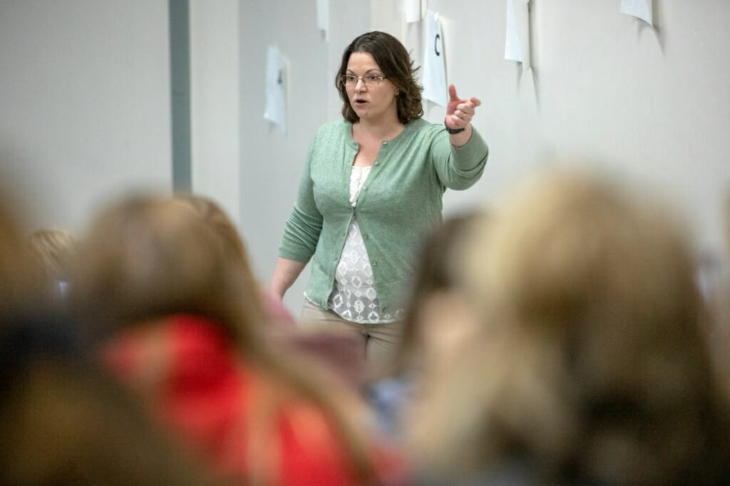 Photo: A woman gesticulates as she speaks to a group of students.