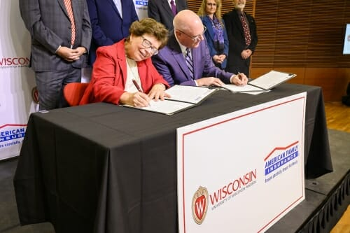 Photo: Blank and Salzwedel sitting at a table signing documents