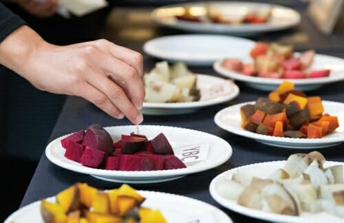 Photo: Plates full of different colored beets on a table.