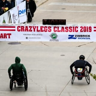 A pair of participants in wheelchairs head up State Street as they start the first wave of the 38th annual Crazylegs Classic.