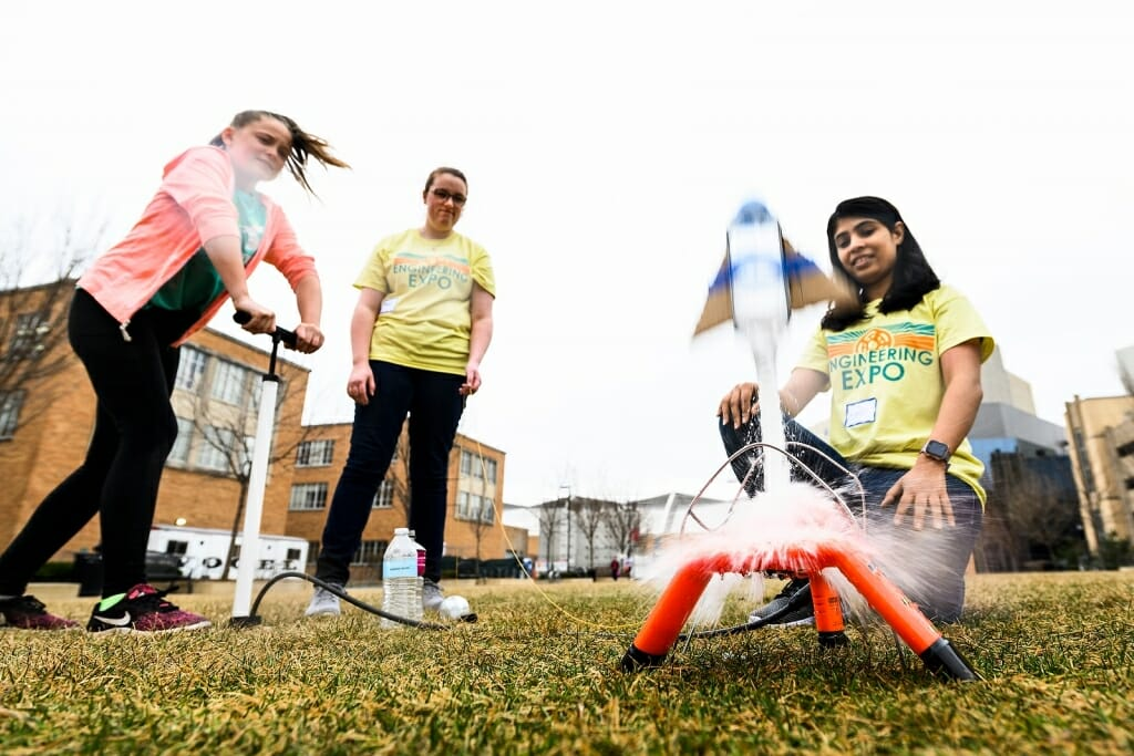 Photo of a child launching a water rocket with help from two students.