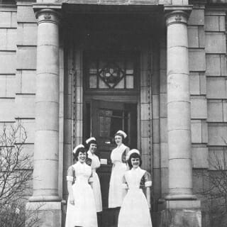 Nursing students pose outside the nursing dorm, in a photo likely from the 1930s.