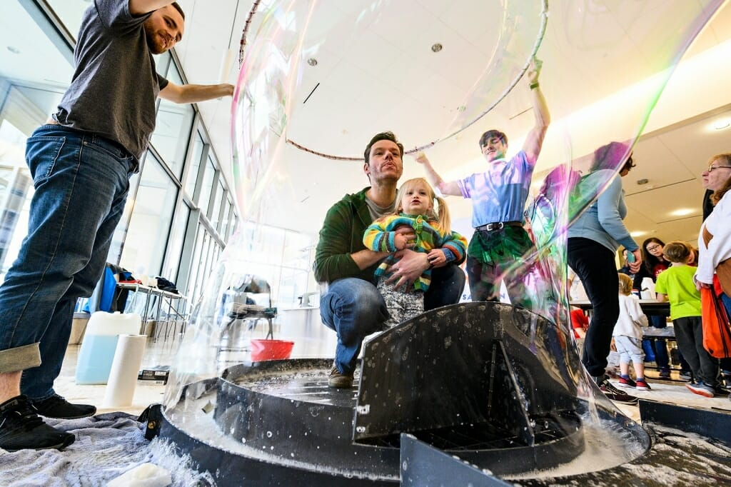 Photo: Father with daughter on lap blow bubbles.