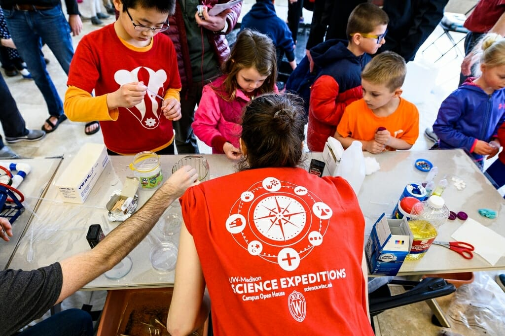 Photo: Kids surround a table with science activities.