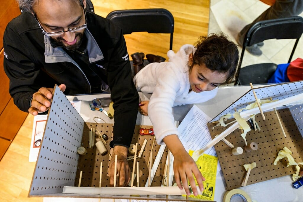 Photo of a father and daughter building a contraption.
