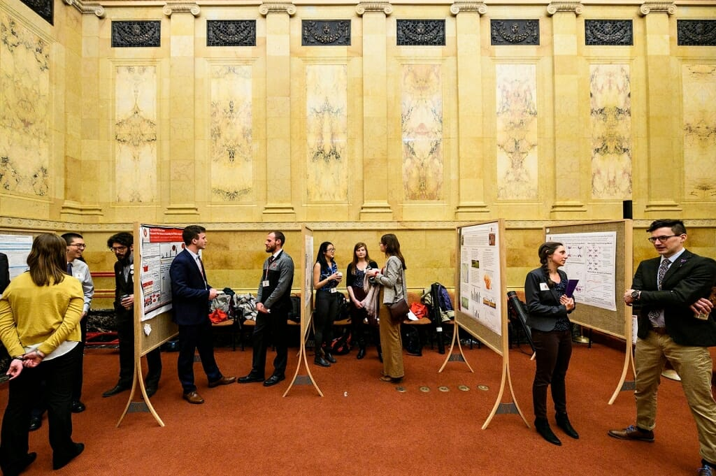 Photo: People standing and conversing in ornate marble hearing room