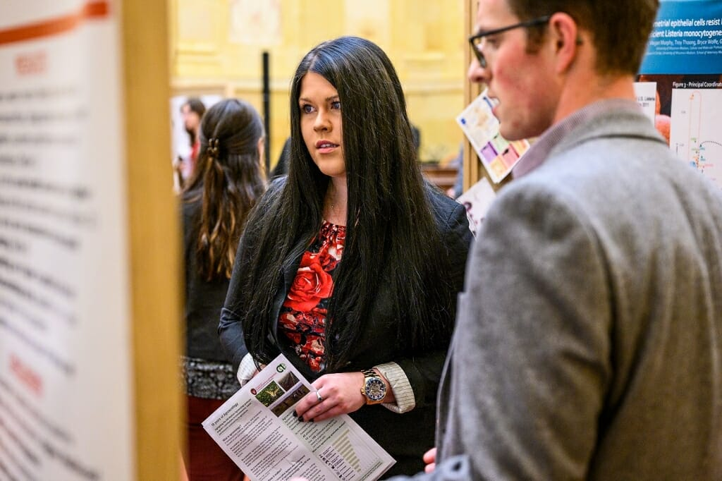 Jacqueline Adamicki, legislative aide to Representative Cindi Duchow, listens as  graduate student Paul Rowley presents information about his radiology research.