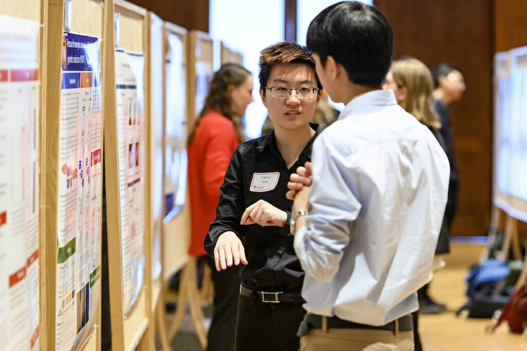 Photo: A student gestures and explains to an onlooker his project, next to a poster board.