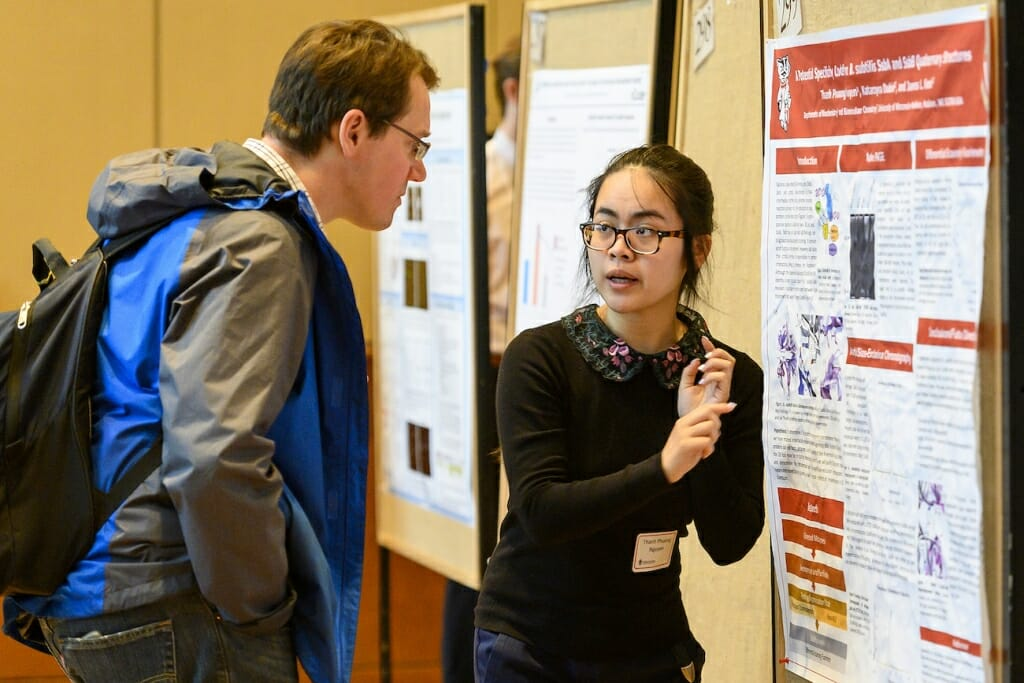 Photo: A student explains to someone her research.