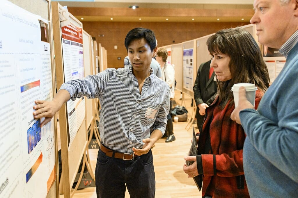 Photo: A student gesticulates as he explains his research.