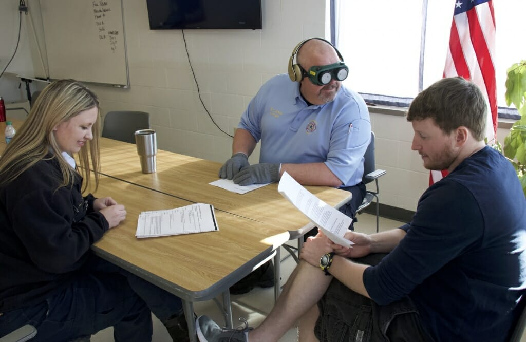 Photo: A man with goggles and earplugs to mimic the effects of dementia speaks with others.