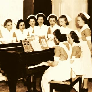 In 1926, nursing students sing around a piano.