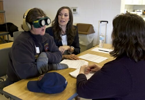 Photo: A man wearing goggles and earplugs talks with two women.