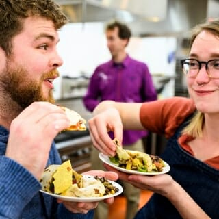 Graduate students Zachary Zalewski and Victoria Lason tentatively sample food with insect ingredients.