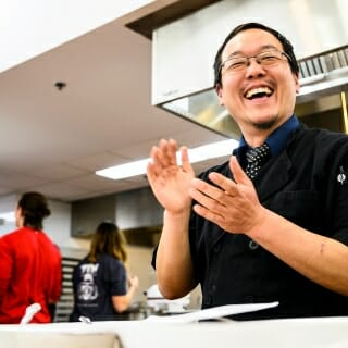 Chef Joseph Yoon cheers on participants as they prepared their dishes with insect ingredients.