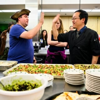 Chef Joseph Yoon, at right, high-fives Matt Blasinski, a technology service consultant in the Division of Information Technology, in recognition of another tasty insect dish.
