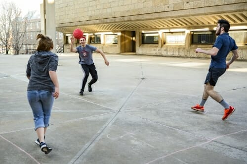 Photo: Three students play with a ball on a concrete surface.