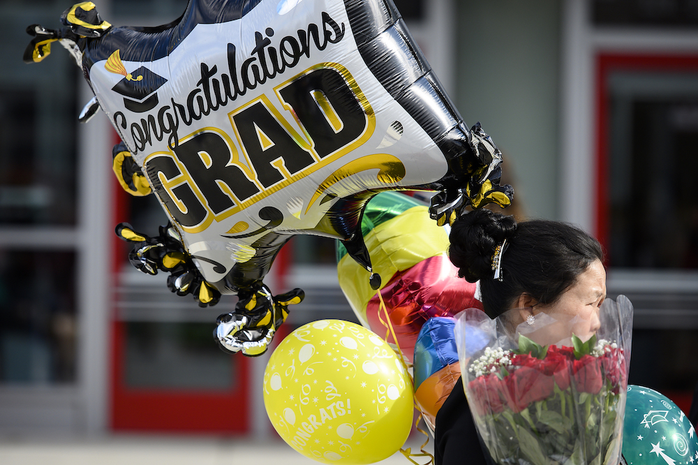 Photo of a woman carrying balloons and flowers.